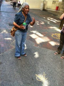 """Lucy, our tour guide, explaining the meaning behind the gold """"VOC"""" emblem in the sidewalk."""
