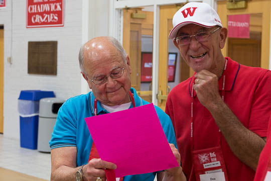 """Bob Witherspoon, song leader for the Class of 1965, and Don Schick check out the """"subdued"""" cheat sheets for Old Wabash."""